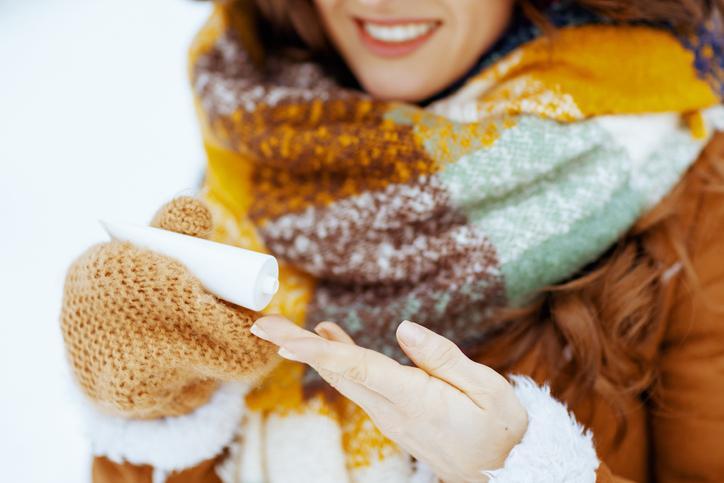kobieta używa kremu do rąk